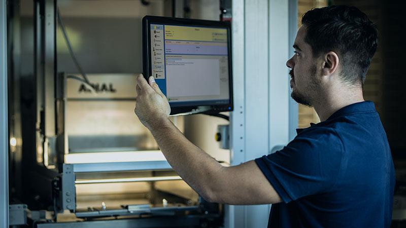 Technicien regardant un écran lors de la maintenance d'un automate